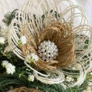 3-layer burlap fabric flower with green, white, and natural layers. With pearl and rhinestone button as center.